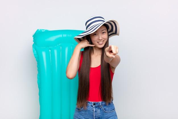 Azjatycka młoda kobieta uśmiecha się wesoło i wskazuje