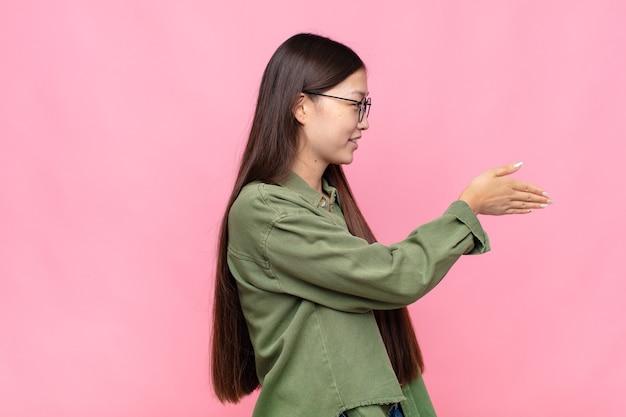 Azjatycka młoda kobieta uśmiecha się, wita i oferuje uścisk dłoni, aby zamknąć udaną transakcję, koncepcja współpracy
