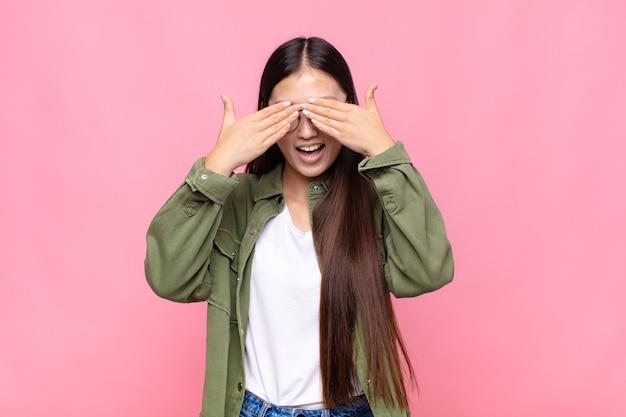 Azjatycka młoda kobieta uśmiechnięta i szczęśliwa, zakrywająca oczy obiema rękami i czekająca na niewiarygodną niespodziankę
