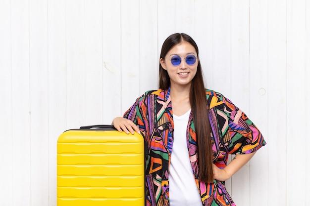 Azjatycka młoda kobieta uśmiechnięta radośnie z ręką na biodrze i pewną siebie, pozytywną, dumną i przyjazną postawą. koncepcja wakacji
