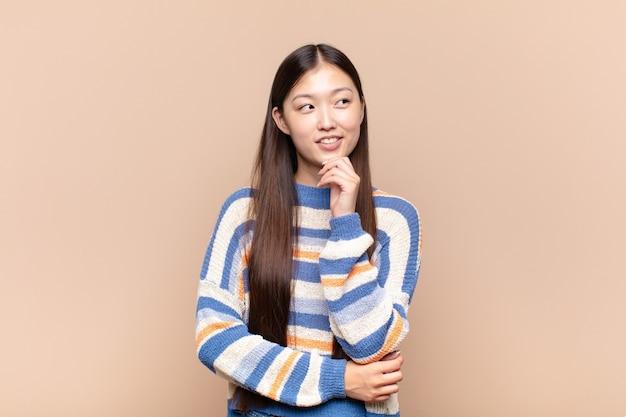 Azjatycka młoda kobieta uśmiechnięta ze szczęśliwym, pewnym siebie wyrazem twarzy z ręką na brodzie, zastanawiająca się i patrząca w bok