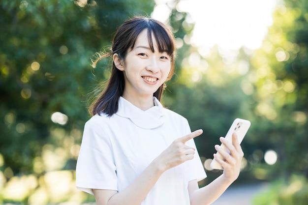 Azjatycka młoda kobieta w białych szatach ze smartfonem
