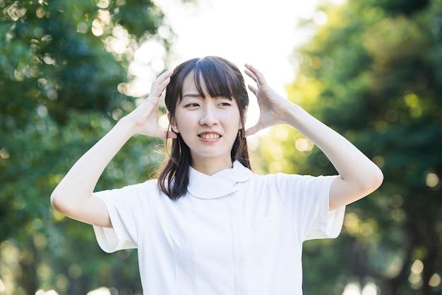 Azjatycka młoda kobieta w białym fartuchu zestresowana