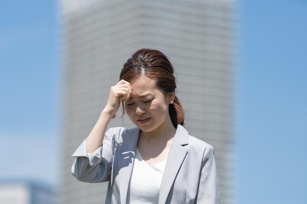 Azjatycka młoda kobieta w biznesowym stroju cierpi od bólu głowy