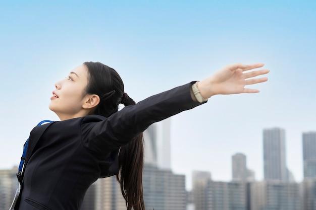 Azjatycka młoda kobieta w garniturze wyciągając rękę i biorąc głęboki oddech
