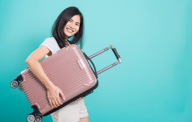 Azjatycka młoda kobieta w koncepcji podróży wakacje jej przytulanie torbę z walizką