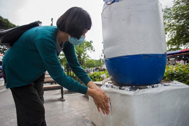 Azjatycka młoda kobieta w masce medycznej do mycia rąk w miejscu publicznym