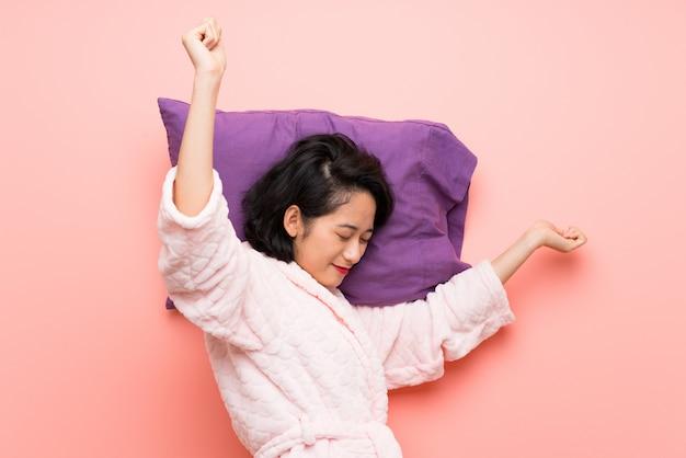 Azjatycka młoda kobieta w piżamy ziewać