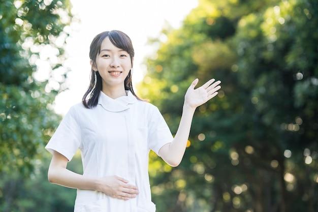 Azjatycka młoda kobieta w ubrania pielęgniarki i pozowanie z rękami