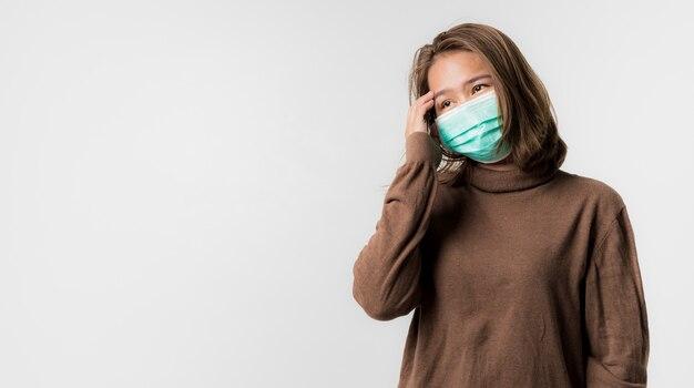 Azjatycka młoda kobieta właścicielka cukierni ubrana w maskę ochronną na twarzy na białym tle, coronavirus covid-19
