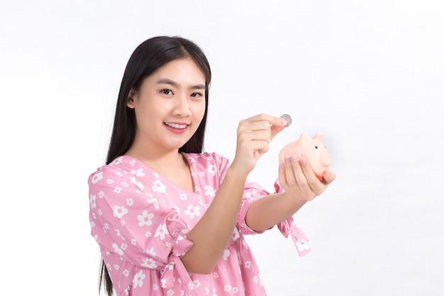 Azjatycka młoda kobieta wrzuca monetę do świnki skarbonki, to jedyny sposób na zaoszczędzenie pieniędzy