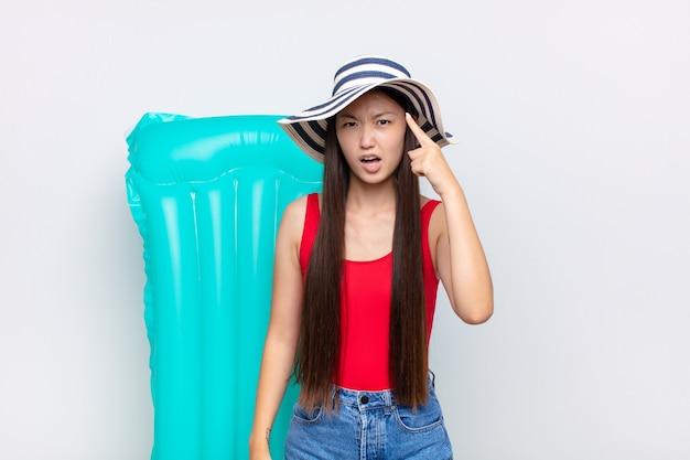 Azjatycka młoda kobieta, wskazując na aparat z gniewnym, agresywnym wyrazem wyglądającym jak wściekły, szalony szef. koncepcja lato