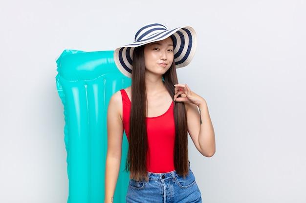Azjatycka młoda kobieta wygląda arogancko, odnosząc sukcesy, pozytywnie i dumnie, wskazując na siebie. koncepcja lato