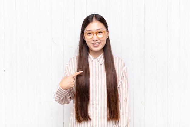 Azjatycka młoda kobieta wygląda dumnie, pewnie i szczęśliwie, uśmiecha się i wskazuje na siebie lub robi znak numer jeden