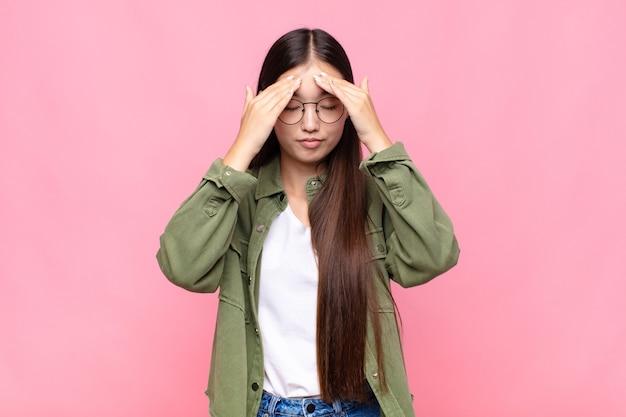 Azjatycka młoda kobieta wygląda na skoncentrowaną, zamyśloną i zainspirowaną