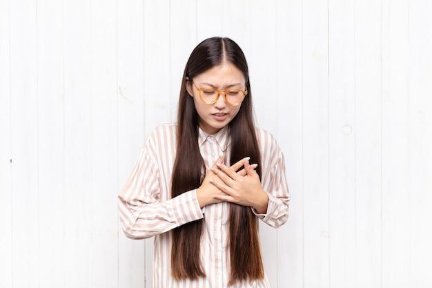Azjatycka młoda kobieta wygląda na smutną, zranioną i załamaną