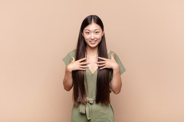 Azjatycka młoda kobieta wygląda na szczęśliwą, zaskoczoną, dumną i podekscytowaną