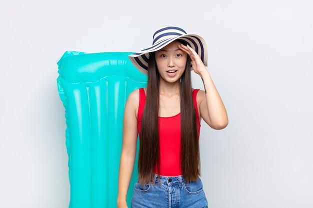 Azjatycka młoda kobieta wygląda na szczęśliwą, zdziwioną i zaskoczoną