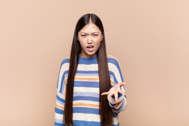Azjatycka młoda kobieta wygląda na wściekłą, zirytowaną i sfrustrowaną krzyczącą