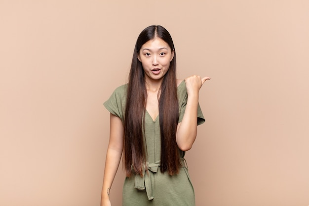 Azjatycka młoda kobieta wygląda na zdumioną z niedowierzaniem