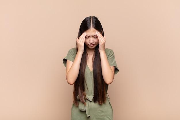 Azjatycka młoda kobieta wygląda na zestresowaną i sfrustrowaną, pracującą pod presją, bóle głowy i kłopoty