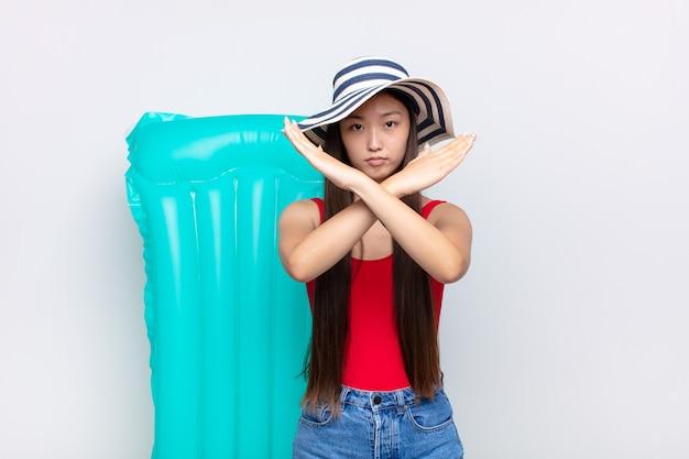Azjatycka młoda kobieta wygląda na zirytowaną i zmęczoną twoją postawą