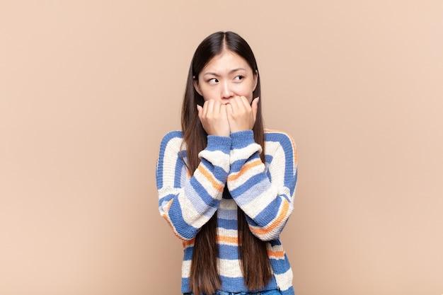 Azjatycka młoda kobieta wygląda na zmartwioną, zaniepokojoną, zestresowaną i przestraszoną