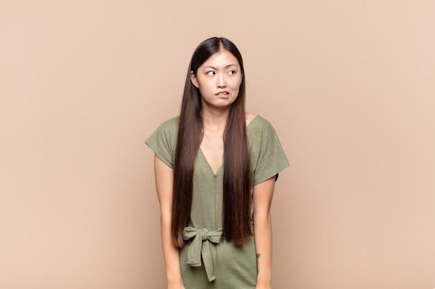 Azjatycka młoda kobieta wygląda na zmartwioną, zestresowaną, niespokojną i przestraszoną