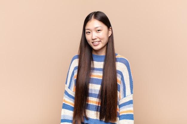 Azjatycka młoda kobieta wyglądająca na dumną, pewną siebie, fajną, bezczelną i arogancką, uśmiechniętą, czującą sukces