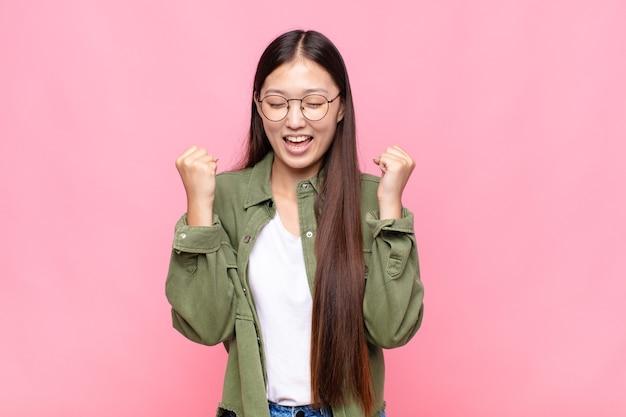 Azjatycka młoda kobieta wyglądająca na niezwykle szczęśliwą i zaskoczoną, świętująca sukces, krzycząca i skacząca