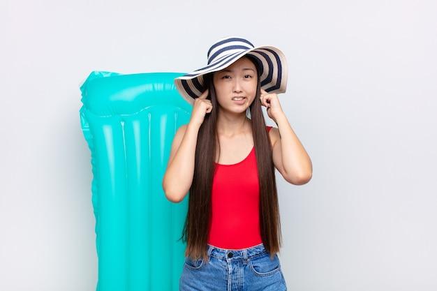 Azjatycka młoda kobieta wyglądająca na rozgniewaną, zestresowaną i zirytowaną, zakrywającą uszy ogłuszającym hałasem, dźwiękiem lub głośną muzyką. koncepcja lato