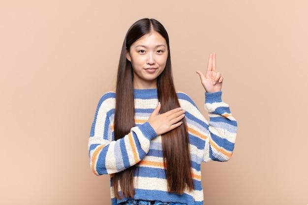 Azjatycka młoda kobieta wyglądająca na szczęśliwą, pewną siebie i godną zaufania, uśmiechniętą i pokazującą znak zwycięstwa, z pozytywnym nastawieniem
