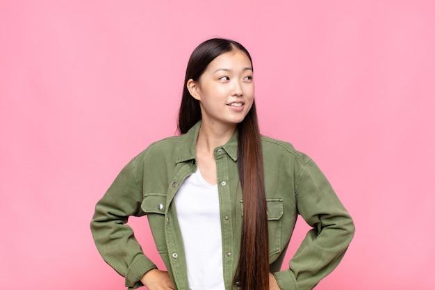 Azjatycka młoda kobieta wyglądająca na szczęśliwą, wesołą i pewną siebie, uśmiechającą się dumnie i patrzącą w bok z obiema rękami na biodrach