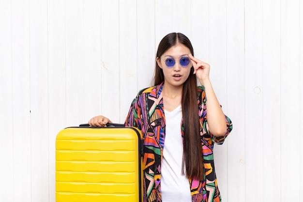 Azjatycka młoda kobieta wyglądająca na zaskoczoną, z otwartymi ustami, zszokowana, uświadamiająca sobie nową myśl, pomysł lub koncepcję. koncepcja wakacji