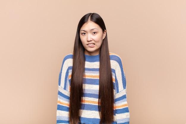 Azjatycka młoda kobieta wyglądająca na zdziwioną i zdezorientowaną, przygryza wargę nerwowym gestem, nie znając odpowiedzi na problem