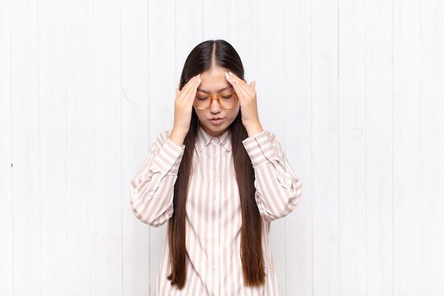 Azjatycka młoda kobieta wyglądająca na zestresowaną i sfrustrowaną, pracującą pod presją, z bólem głowy i z problemami