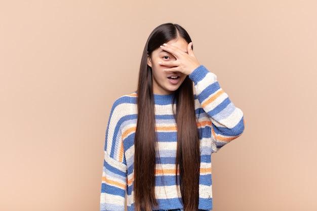 Azjatycka młoda kobieta wyglądająca na zszokowaną, przestraszoną lub przerażoną, zakrywającą twarz dłonią i zerkającą między palcami