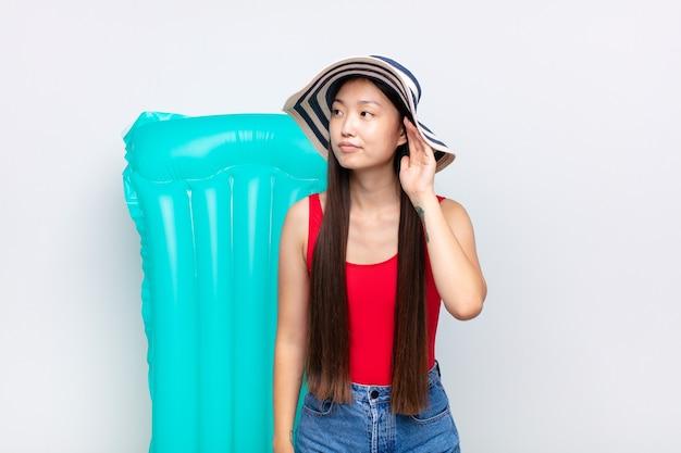 Azjatycka młoda kobieta wyglądająca poważnie i zaciekawiona, słuchająca, próbująca usłyszeć tajną rozmowę lub plotkę