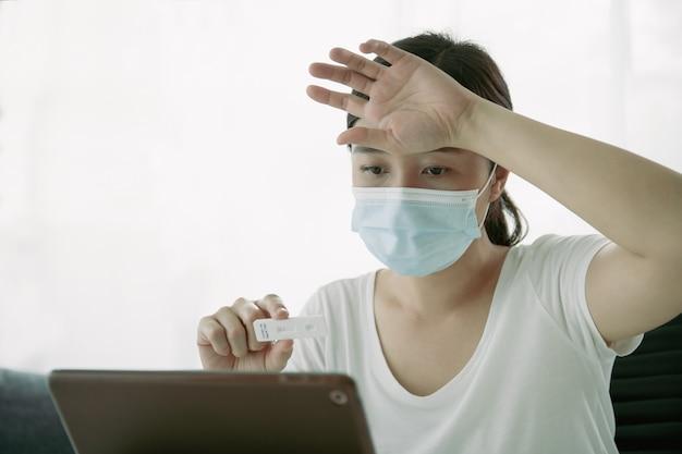 Azjatycka młoda kobieta z higieniczną maseczką ochronną przy użyciu zestawu do szybkiego testu sars 2019-ncov covid-19 antygenu koronawirusa - zestaw do testu na ag w domu i konsultowanie wyniku badania z lekarzem przez rozmowę wideo.