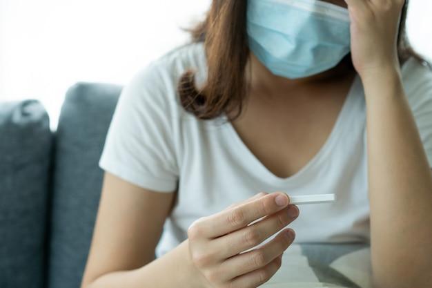 Azjatycka młoda kobieta z higieniczną maską ochronną na twarz przy użyciu zestawu do szybkiego testu sars 2019-ncov covid-19 koronawirusa antygenu - zestaw do testu ag w domu. szybki test na obecność antygenu covid-19.
