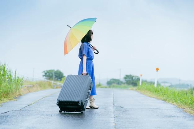 Azjatycka młoda kobieta z walizką i kolorowym parasolem