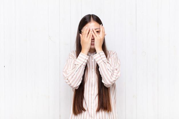 Azjatycka młoda kobieta zakrywająca twarz rękami, zaglądająca między palce ze zdziwieniem i patrząc w bok