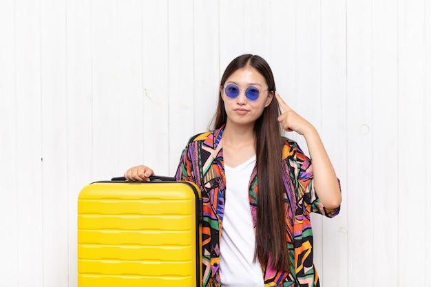 Azjatycka młoda kobieta ze złym nastawieniem wyglądająca dumnie i agresywnie, wskazująca w górę lub śmiejąca się znak rękami. koncepcja wakacji