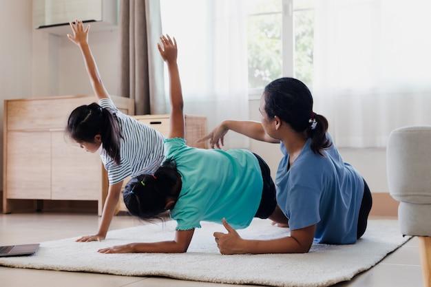 Azjatycka młoda matka i jej córki razem robi ćwiczenia rozciągające fitness jogi w domu. rodzice i dzieci starają się być silni i dbać o zdrowie fizyczne i dobre samopoczucie w codziennej rutynie.