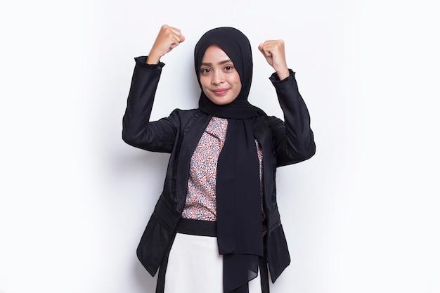 Azjatycka młoda muzułmańska kobieta biznesu szczęśliwa i podekscytowana świętuje zwycięstwo, wyrażając wielki sukces