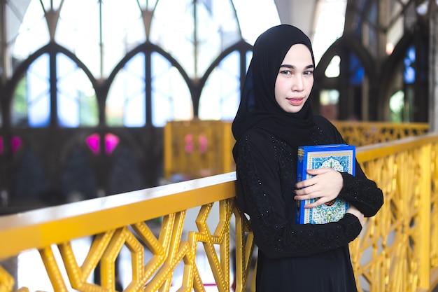 Azjatycka młoda muzułmańska kobieta jest ubranym hidżab czerni suknię trzyma koran, w meczecie.