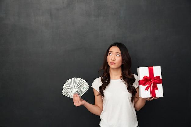 Azjatycka młoda myśląca kobieta trzyma pieniądze i prezenta pudełko