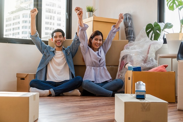 Azjatycka młoda para cieszy się po pomyślnym zapakowaniu dużego kartonowego pudła do przeprowadzki