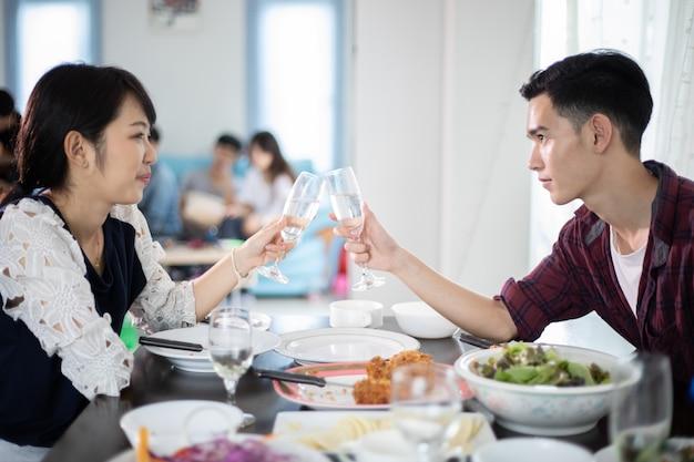 Azjatycka młoda para cieszy się romantycznego obiadowego wieczór pije podczas gdy siedzący przy jadalnią