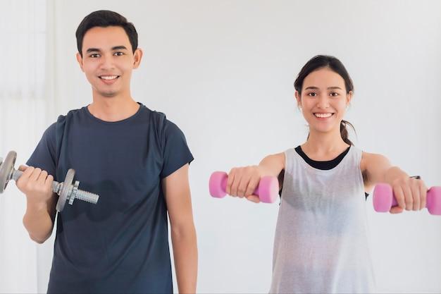Azjatycka młoda para ćwiczy razem w domu w tle. koncepcja ćwiczeń podczas kwarantanny w domu w celu zapobiegania zakażeniu koronawirusem i covid-19.